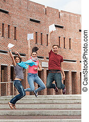 Happy students jumping in the air holding exam in school