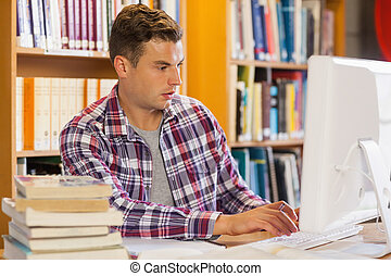 Handsome focused student using computer in library