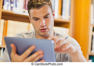 Attractive serious student using tablet in library