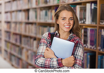 Pretty cheerful student holding tablet in library