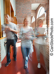 Students walking through hallway toward camera in school