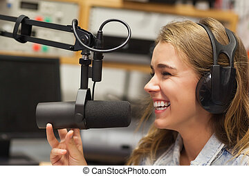 Laughing pretty radio host moderating sitting in studio at...