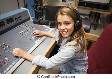 Smiling pretty radio host moderating sitting in studio at...