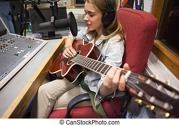Focused pretty singer recording and playing guitar in studio...