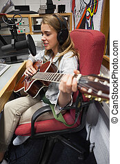 Concentrating pretty singer recording and playing guitar in...