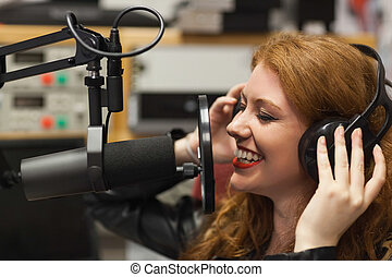 Cheerful beautiful singer recording a song in studio at...