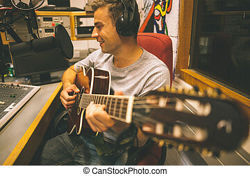 Smiling handsome singer recording and playing guitar in...