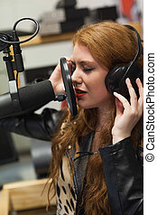 Concentrating beautiful singer recording a song in studio at...
