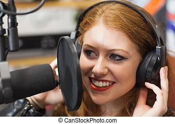 Happy beautiful singer recording a song in studio at college