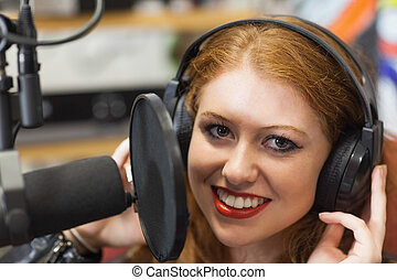 Smiling beautiful singer recording a song in studio at...