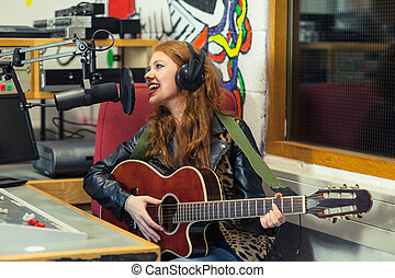 Cheerful beautiful singer recording and playing guitar in...