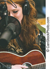 Content beautiful singer recording and playing guitar in...