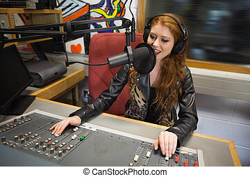 Happy beautiful radio host moderating sitting in studio at...