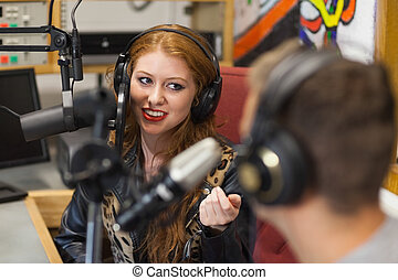 Attractive happy radio host interviewing a guest in studio...
