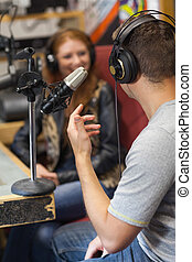 Attractive smiling radio host interviewing a guest in studio...
