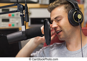 Handsome focused singer recording a song in studio at...