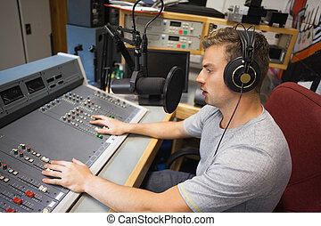 Handsome focused radio host moderating in studio at college