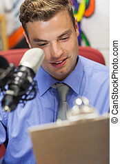 Well dressed smiling radio host moderating holding clipboard