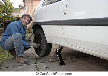 tire puncture - Man tighten the bolts until they are seated