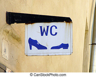 Toilet sign - A white toilet sign with blue text with a...