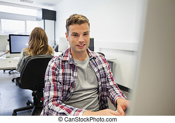 Handsome smiling student working on computer