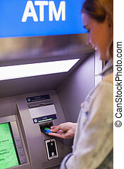 Pretty student withdrawing cash at an ATM