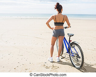 Rear view of a woman with bike on beach - Rear view of...