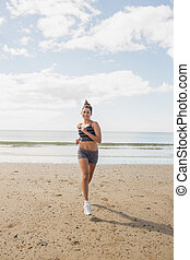 Sporty brunette woman jogging on the beach in bright...
