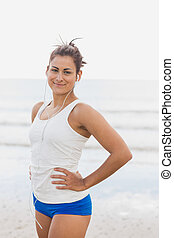 Woman listening to music through earphones at beach -...