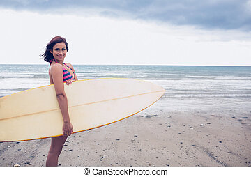 Smiling woman carrying surfboard on the beach - Side view of...