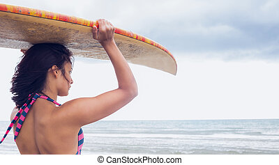 Woman carrying surfboard on head at beach
