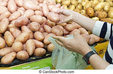 Buying vegetables - Shopper packing or buying potatoes...