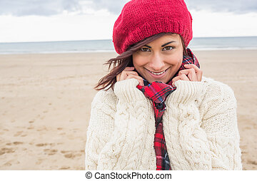 Cute smiling woman in stylish warm clothing on the beach -...