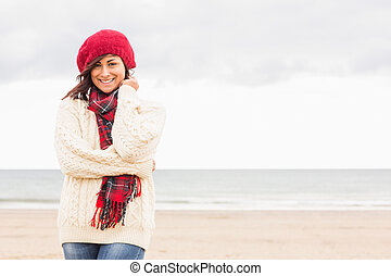 Cute smiling woman in stylish warm clothing at beach -...