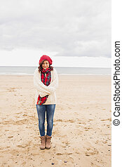 Pretty woman in stylish warm clothing at beach - Full length...