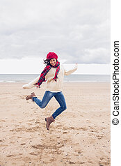 Woman in stylish warm clothing jump - Full length of a woman...