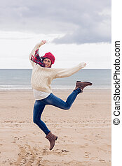 Woman in stylish warm clothing jumping at beach - Full...