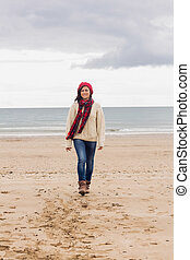 Full length of a woman in stylish warm clothing at beach -...