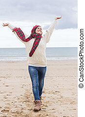 Woman in warm clothing stretching her arms at beach
