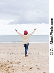 Woman in casual warm wear stretching arms on beach - Full...