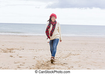Pretty woman in stylish warm wear at beach - Full length of...