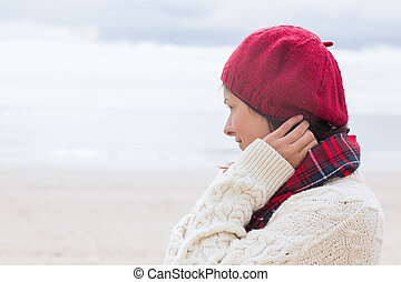Woman in knitted hat and pullover at beach - Close-up side...