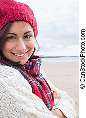 Woman in knitted hat and pullover smiling at beach - Close...