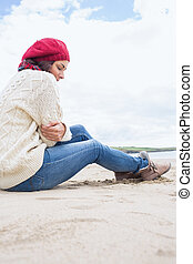 Woman in stylish warm clothing sitting at beach - Side view...