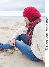 Woman in stylish warm clothing sitting at the beach - Side...