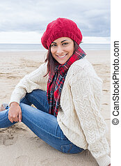 Smiling woman in stylish warm clothing sitting on beach -...