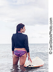 Rear view of a woman with surfboard in water - Rear view of...