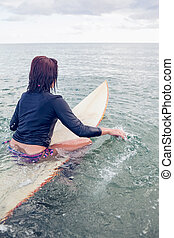 Rear view of a woman sitting on surfboard in the water at...