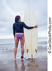 Rear view of a calm woman with surfboard on beach - Full...