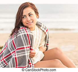 Beautiful woman covering herself with blanket at beach -...